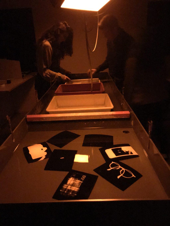 Elena og Kristian fremkaller fotogrammer. I forgrunn har vi fotogrammer i skyllekaret.